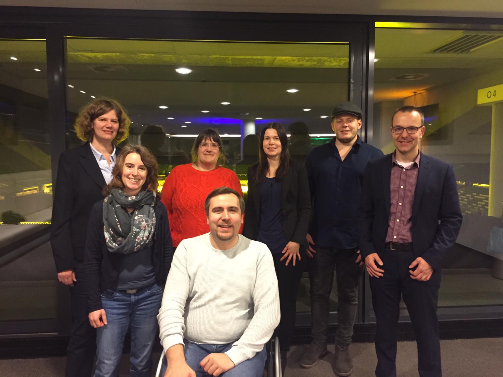 Auf dem Bild sind von links nach rechts zu sehen: Ulrike Peter, Julia Finken, Rebecca Romppel, Benjamin Tannert, Tatjana Menke, Tim Wessel, Kai Steuck. Sie stehen vor einem Fenster mit Blick in das Weserstadion.