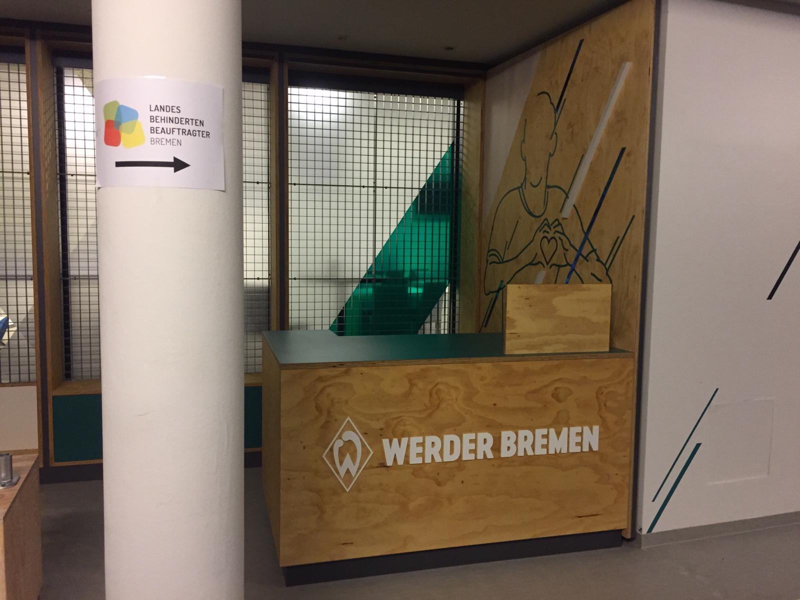 Auf dem Bild sieht man eine Säule, auf der das Logo des Landesbehindertenbeauftragten Bremen als Wegweiser befestigt ist. Die Säule steht neben einer Holzverkleidung mit dem Logo von Werder Bremen.