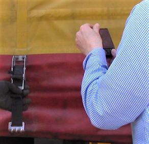 Auf dem Bild sieht man eine Person, die ein Foto davon macht, wie eine andere person die Schnalle einer LKW-Plane öffnet.
